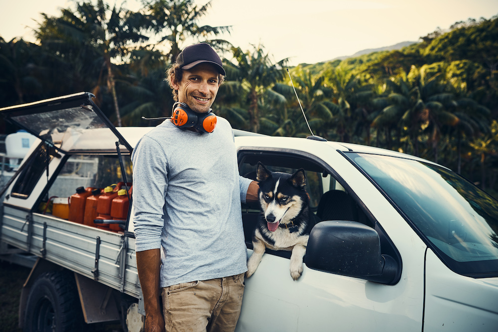 Portrait of a happy landscaper petting his dog while standing next to his vehicle